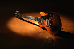 Electric Guitar. Music concept.Electric guitar on wooden surface under beam of light Royalty Free Stock Photo