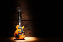 Electric Guitar. Music concept.Electric guitar standing near wooden wall under beam of light Royalty Free Stock Image