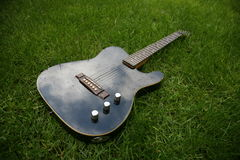 Electric guitar. Black vintage in grass Royalty Free Stock Image