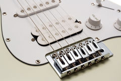 Electric Guitar. Close up of the Bridge and Strings of a white electric guitar. Isolated on White royalty free stock photo