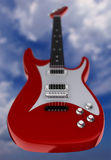 Electric guitar. A red electric guitar on cloudy sky background - focus on foreground of guitar - 3d render Stock Image
