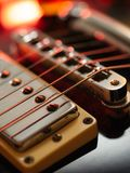 Electric guitar abstract. Macro abstract photo of the pickups, bridge and strings of an electric guitar. Shallow depth of field with focus on the first string Royalty Free Stock Image