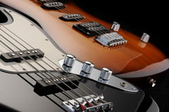 Electric guitar and bass. A close up of a electric guitar , and of a black bass glossy on dark background stock photo