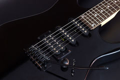 Electric guitar. Black electric guitar close up on dark background Royalty Free Stock Image