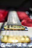 Electric guitar blur. Angled shot of a white electric guitar, with the focus on the neck pickup Royalty Free Stock Image