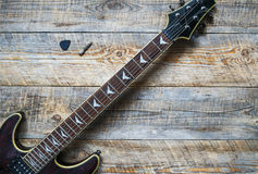 Electric guitar body on wooden board background. Royalty Free Stock Photography