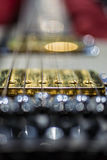 Electric guitar bridge pickup blur. A close-up of a gold bridge pickup on an electric guitar, with a blurred foreground and background Royalty Free Stock Photos