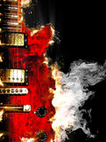 Electric guitar burning in fire. Music concept with burn in fire and smoke design red electric guitar isolated on black background in dark Stock Photography