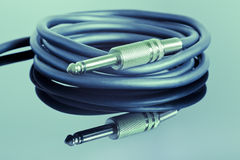 Electric guitar cable. On a split tone background Royalty Free Stock Image