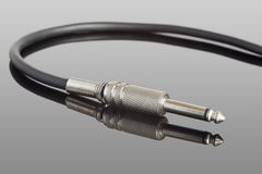 Electric guitar cable. On a reflective surface Royalty Free Stock Photography