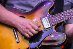 Electric Guitar Strum. Chord being played on vintage glossy sunburst electric guitar. Guitar shows signs of wear stock photo