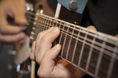 Electric guitar close-up with fingers playing it Royalty Free Stock Image