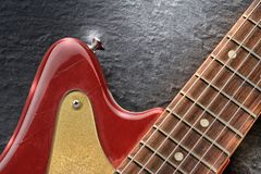 Electric guitar close up shines on slate background. Electric guitar close up, colored in red and gold, it contrasts with the black slate background Stock Image