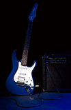 Electric guitar and combo amplifier. In rays of blue light on black background Royalty Free Stock Photo