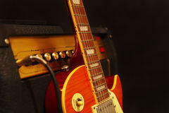 Electric guitar with combo amplifier on black background. Shallow depth of field, low key, close up. Stock Photos