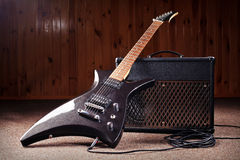 Electric guitar and combos. Black electric guitar stand in front of amplifier Stock Photos