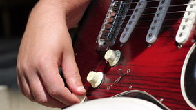 Electric Guitar Control Knobs. Tuning the volume and tone knobs on an electric guitar.  Starting with the lower aft knob (the one closest to the input jack) and stock video footage