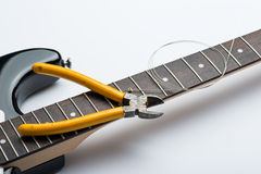 Electric guitar frets with string and yellow nippers. Guitar frets with string and yellow nippers Royalty Free Stock Images