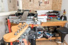 Electric guitar in handmade domestic music instrument service repair made in garage. On special slider table close up selective stock photography