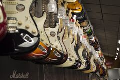 Electric Guitar Hanging Near Wall Stock Photo