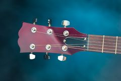 Electric guitar head, blue background Royalty Free Stock Photos