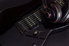 Electric guitar. Headphone on black electric guitar in darkness royalty free stock image