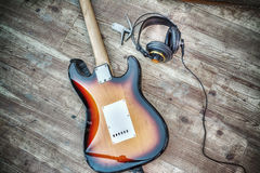 Electric guitar and headphones on a wooden board in hdr Stock Image