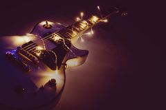 Electric guitar with lighted garland. On dark background. Gift guitar classic shapes for Christmas or new year stock images