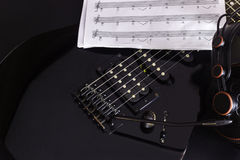 Electric guitar. Music note, Headphone and electric guitar on black background royalty free stock photography