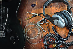 Electric guitar and musical accessories. Musical still life with a guitar, with earphones, guitar strings and a kapodaster Royalty Free Stock Image