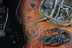 Electric guitar and musical accessories. Musical still life with a guitar, with earphones, guitar strings and the microphone Stock Photos