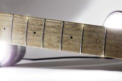 Electric guitar neck fingerboard under studio lighting. Electric guitar neck. Maple fingerboard under studio lighting with lens flare Royalty Free Stock Photos