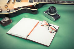 Electric guitar with notepads, pencil, glasses and old camera on a green background. Filtered retro image Royalty Free Stock Image