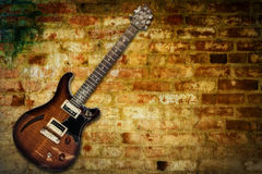 Electric guitar. Old derelict wall with electric guitar against grunge background brickwork with path stock images
