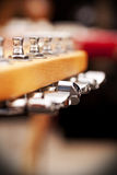Electric guitar pegbox. With selective focus on the central peg Stock Photo