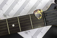 Electric guitar. Guitar pick on fretboard with music note on black background royalty free stock photo