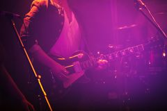 Electric guitar player in purple light Royalty Free Stock Images