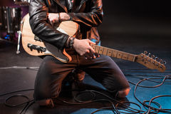 Electric guitar player kneeling with bass guitar on stage. Cropped shot of electric guitar player kneeling with bass guitar on stage stock photography