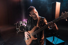 Electric guitar player performing hard rock music with bass guitar. On stage royalty free stock image