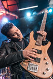 Electric guitar player playing hard rock music with bass guitar. On stage stock photography