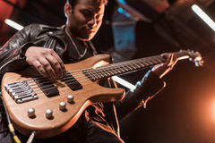 Electric guitar player playing hard rock music with bass guitar. On stage royalty free stock photography