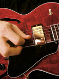 Electric guitar playing. Jazz musician playing red electric guitar royalty free stock photography
