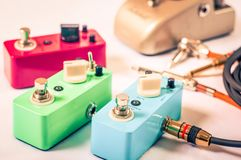 Electric guitar stomp effectors and cables in studio. Focus is on forehand switch box. Setting up guitar audio processing effects. Electric guitar stomp box Royalty Free Stock Image
