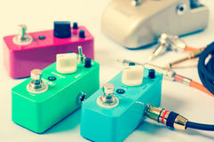 Electric guitar stomp effectors and cables in studio. Focus is on forehand switch box. Stock Images