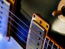 Electric guitar strings and pickups. Macro abstract photo of the pickups and strings of an electric guitar. Shallow depth of field with focus on the first string royalty free stock photos