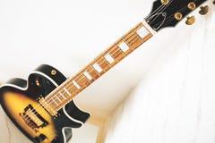 Electric guitar. Electric sunburst guitar in white brick corner. Music concept stock photography