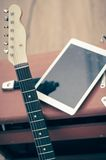 Electric guitar with white tablet. Royalty Free Stock Images