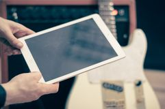 Electric guitar with white tablet. Stock Images