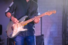 Electric guitarist on stage for background with colorful blue an stock image