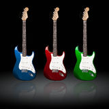 Electric guitars. Three electric guitars of different colors with reflections Stock Image